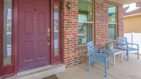 一个家的清楚的全景门面有一个红色大门的和反射性侧灯和窗口 库存照片