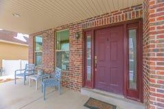 一个家的门面有一个红色大门的和反射性侧灯和窗口 免版税库存照片