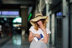 一个宽充满的帽子的俏丽的女孩有护照的和票在手上 图库摄影