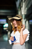 一个宽充满的帽子的俏丽的女孩有护照的和票在手上 库存照片