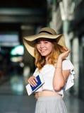 一个宽充满的帽子的俏丽的女孩有护照的和票在手上 免版税库存图片