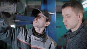 一个对一辆汽车的车主的专业技术员谈话关于修理他的车的在轮胎配件购物 股票录像
