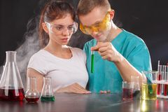 一个对化学家,审查在一个小透明烧瓶的绿色液体 科学的概念 免版税库存照片