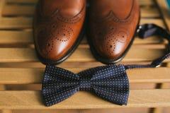一个对在一把椅子的棕色时髦的皮革人` s方鞋子在一个蓝色蝶形领结旁边 新郎的辅助部件 库存照片