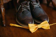 一个对在一把椅子的棕色时髦的皮革人` s方鞋子在一个黄色蝶形领结旁边 新郎的辅助部件 免版税库存照片