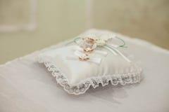 一个对在一点逗人喜爱的鞋带的婚戒把枕在与丝绸ri 库存照片