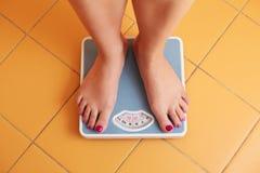 一个对在体重计的女性脚 免版税库存照片