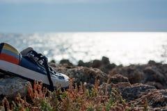 一个对在岩石的体育鞋子在海前面 免版税库存照片