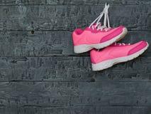 一个对在木墙壁的背景的桃红色体育鞋子 图库摄影