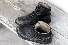 一个对在木桌上的老鞋子 图库摄影