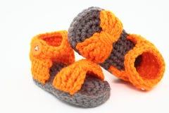 一个对在橙色和灰色的被手工造的婴孩凉鞋 免版税库存图片