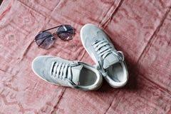 一个对在白色脚底与白色口音和太阳镜的蓝色绒面革运动鞋有在桃红色背景的蓝色玻璃的 免版税库存图片
