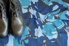 一个对在织品的黑军队起动与与copispace的蓝色伪装文本的 图库摄影