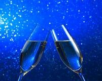 一个对在蓝色轻的bokeh背景的香槟槽 免版税库存图片