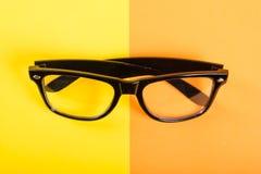 一个对在黄色和橙色背景的黑玻璃 免版税库存照片