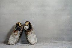 一个对在水泥背景,老背景,老起动的老鞋子 免版税库存图片