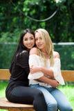 一个对户外的骄傲的女同性恋者坐一张木桌,深色的妇女在庭院里拥抱一名白肤金发的妇女, 库存照片