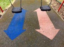 一个对摇摆和箭头在孩子操场 库存图片