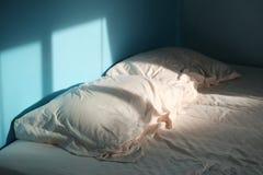 一个对有一个床单的起皱纹的枕头在蓝色室和早晨光 免版税库存图片