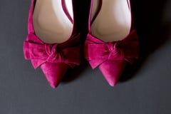一个对有丝带和灰色背景的桃红色妇女鞋子 免版税库存图片