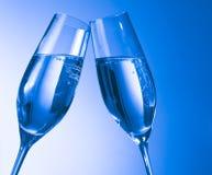 一个对有金黄泡影的香槟槽在蓝色轻的背景 库存图片