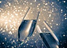 一个对有金黄泡影的香槟槽在蓝色轻的bokeh背景 免版税库存图片