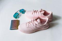 一个对桃红色皮革运动鞋、一个钱包有多彩多姿的衣服饰物之小金属片的和太阳镜有蓝色玻璃的在白色背景 免版税库存图片