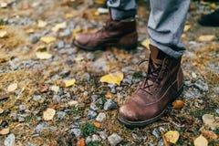 一个对棕色远足的起动在秋天森林软的焦点在起动 免版税库存照片