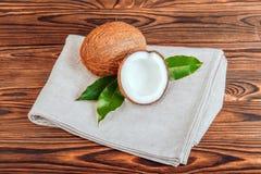 一个对椰子和绿色在一种灰色织品离开 一个整体和裁减椰子在木背景 甜有机点心 库存图片