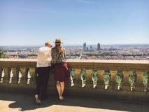 一个对男人和妇女站立与他们的后面并且看从高峰的全景到市利昂在法国  库存照片