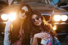 一个对的室外生活方式画象戴太阳镜的最好的朋友相当女孩,佩带一个明亮的牺牲者 图库摄影