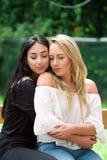 一个对骄傲的女同性恋者户外,深色的妇女拥抱一名白肤金发的妇女,在庭院背景中 库存图片