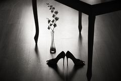 一个对高跟鞋和一朵花在桌下 免版税库存照片