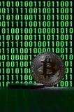 一个对bitcoins说谎在描述鲜绿色的零的二进制编码显示器的背景的纸板表面上和 免版税库存图片