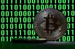 一个对bitcoins说谎在描述鲜绿色的零的二进制编码显示器的背景的纸板表面上和 库存图片