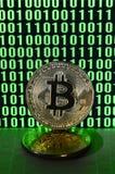 一个对bitcoins说谎在描述鲜绿色的零的二进制编码显示器的背景的纸板表面上和 图库摄影