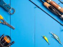 一个对spinnings、一个卷轴和诱剂在一蓝色木backgroun 免版税库存照片
