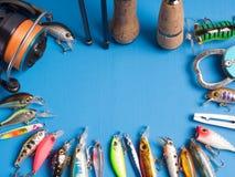 一个对spinnings、一个卷轴和诱饵和工具在木的蓝色 库存图片