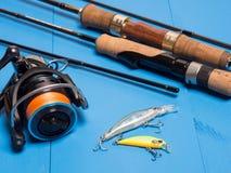 一个对spinnings、一个卷轴和诱饵在一蓝色木backgroun 免版税图库摄影