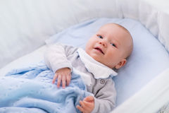 一个小儿床的男婴在被编织的毯子下 图库摄影