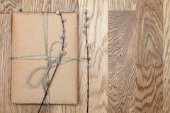 一个小包或箱子在eco纸在木桌上 顶视图 礼物盒栓与麻线 免版税库存照片