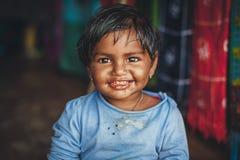 一个小印度女孩看照相机和微笑摄影师 免版税图库摄影