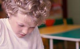 一个小卷曲白种人男孩下面看某事,当坐在一张桌上在儿童` s屋子时 免版税库存图片