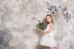 一个小可爱的女孩的画象一件白色礼服的有花束的在她的手上以难看的东西墙壁为背景 库存照片