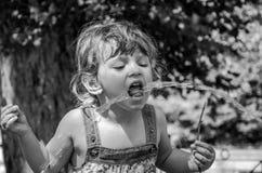 一个小可爱的小女孩,礼服的,饮料一个婴孩从一台罗马饮水器的喷口浇灌在一个热的夏日, quen 库存图片