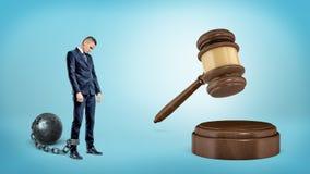 一个小哀伤的商人leashed对铁球立场在一根巨型击中的法官惊堂木附近 免版税库存图片
