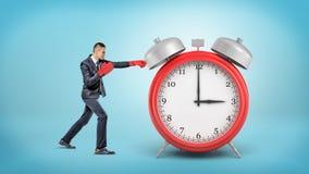一个小商人戴着拳击手套并且猛击一个巨型红色闹钟 免版税库存照片