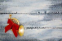 一个小喇叭,有一把红色弓的一块垫铁在破旧的蓝色木背景 圣诞节装饰生态学木 免版税库存照片