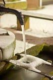 一个小喷泉在冬天在与冰和雪的晚上 免版税库存照片