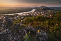 一个小城市和一条河的看法有岩石的在前景 免版税库存照片